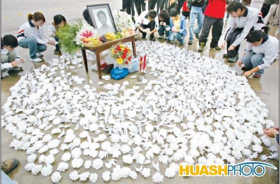 同学们将千纸鹤和小白花摆放成心形图案以纪念救人英雄李恒太 本报